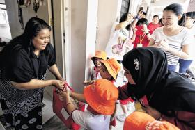 PCF Sparkletots pre-schoolers, accompanied by Tampines GRC MP Cheng Li Hui, giving a bag of provisions to housewife Julianah Sani, on Saturday.