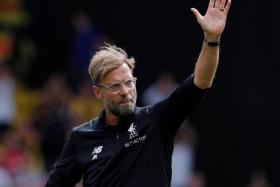 Juergen Klopp waves to the fans at the end of the match against Watford