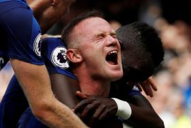 Everton's Wayne Rooney celebrating with teammates after scoring their first goal.