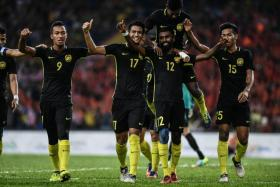 Malaysia's players celebrate scoring a goal against Myanmar during their men's football match at the 29th Southeast Asian Games.