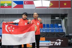 Singapore's Chan Keng Kwang (left) and Tey Choon Kiat holding up their gold medals after defeating their Thai opponents in the SEA Games men's snooker doubles final at the Kuala Lumpur Convention Centre.