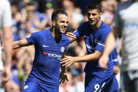 Chelsea's Cesc Fabregas (L) celebrates with teammate Alvaro Morata (R) after scoring a goal during the English Premier League soccer match between Chelsea and Everton at Stamford Bridge