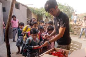 Mr Haziq Rashid distributing supplies to children in Roopsi village in Jaisalmer, India.