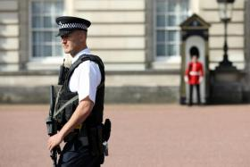 A police officer patrols within the grounds of Buckingham Palace in London