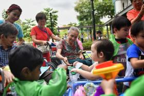 Nursing home residents and children interact under supervision at the inter- generational playground of St Joseph's Home