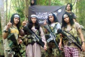 Hajar Abdul Mubin (left) - otherwise known as Abu Asrie - in an undated photo taken in the southern Philippines. Hajar, a Filipino, was arrested along with one other Filipino and six Malaysians from the Borneo state of Sabah in a raid last Wednesday.