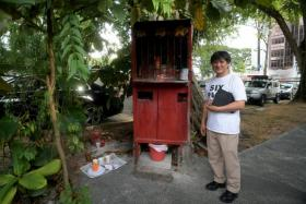 Mr Charles Goh with the shrine erected in honour of Madam Huang Su Ying. It now needs to be removed due to redevelopment works.