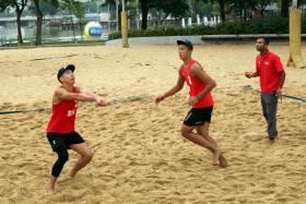 Gilbert Tan setting the ball for Zhuo Hong Chuan in training, as national beach volleyball coach Dean Martin instructs them.