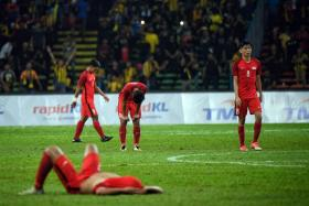 The Singapore's national Under-22 players looking crestfallen after the final whistle in their 2-1 defeat by Malaysia in the SEA Games Group A football match at Shah Alam Stadium in Malaysia.