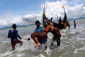 Smoke is seen on Myanmar's side of border as an exhausted Rohingya refugee woman is carried to the shore after crossing the Bangladesh-Myanmar border by boat through the Bay of Bengal, in Shah Porir Dwip, Bangladesh on Sept 11, 2017.