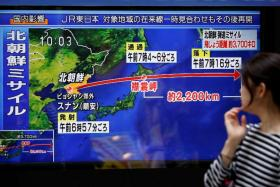 A passerby looks at a TV screen reporting news about North Korea's missile launch in Tokyo, Japan Sept 15, 2017.