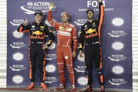 Ferrari's Sebastian Vettel (centre) secures pole position beside Red Bull's Max Verstappen (left) and Daniel Ricciardo after the qualifying session of the Formula One Singapore Grand Prix.
