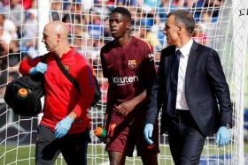 Ousmane Dembele is escorted from the field after sustaining an injury during Barcelona's La Liga match against Getafe.