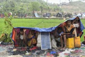 Rohingya refugees sheltering from the rain in a Bangladeshi refugee camp.