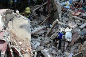 Rescuers, firefighters, policemen, soldiers and volunteers remove rubble and debris from a flattened building in search of survivors after a powerful quake in Mexico City