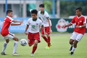 Singapore U-15 players Ilhan Fandi (far left) and Izwan Chik Awang (far right) in action against Indonesia in the 2-0 loss at the AFF U-15 Championship in July.