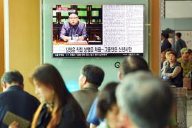 Commuters at a railway station in Seoul watching a television news screen showing North Korean leader Kim Jong Un delivering a statement in Pyongyang.