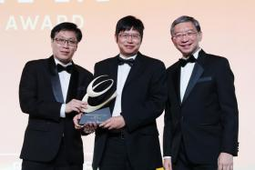 Ace Water managing director Tian Xianyong (centre), receiving his award from Business Times editor Wong Wei Kong (left) and Mr Linus Goh (right) of OCBC Bank.