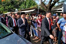 President Joko Widodo waving after getting out of his car.