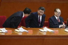 Chinese President Xi Jinping (centre) taking a seat between former presidents Jiang Zemin (right) and Hu Jintao.