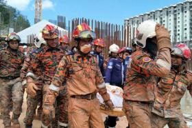 Rescue workers carrying out the body of a victim of the landslide in Tanjung Bungah, Penang.