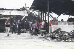 Indonesian forensic police officers inspecting the site of a deadly fireworks factory fire outside Jakarta.
