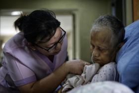 Senior nurse Liew Seenah assisting Madam Pungut Jumadi at Green Acres nursing home in Johor Baru.