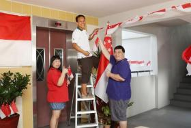 Mr Hamzah Osman (middle) pays for and personally decorates his Housing Board flat corridor and elevator lobby for holidays and festive occasions.