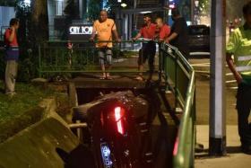 Car crashes into drain after hitting man