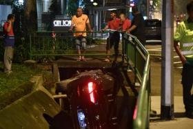 Car crashes into drain after hitting man