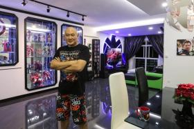 Displayed in a floor-to-ceiling cabinet in the living room are 21 superhero figurines Mr Jason Koh bought for $7,000.