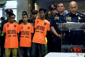 Philippine National Police director general Ronald Dela Rosa (right) speaking during a press conference as three alleged plotters are displayed to the media.