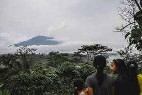 Local residents look on as Mount Agung spews smoke, as seen from Karangasem, Bali.