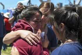 A relative of one of the sub's crew members of being comforted outside the navy base in Mar del Plata,