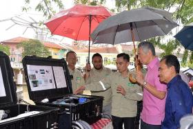 Prime Minister Lee Hsien Loong being briefed on the water treatment process with Berita Harian editor Saat Abdul Rahman (in blue).