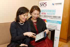 Ms Irene Soon and Ms Megan Ong looking at the upcoming digital commerce course co-offered by NYP-SIRS and Amazon Web Services.