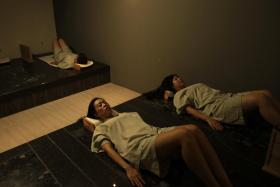Customers lie on heated volcanic rock beds for an hour and the treatment is said to help the body release toxins through perspiration.