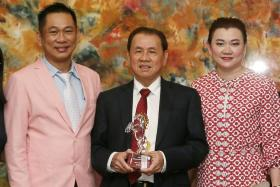 Thai owner Preecha Chaisirinon of Kajorn Petch Racing No. 2 Stable holding the 2017 Horse of the Year award won by Infantry, flanked by his daughter Benjaporn and trainer Alwin Tan last night.
