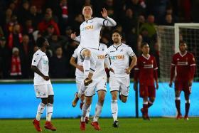 Swansea City's English defender Alfie Mawson (C) celebrates after scoring against Liverpool.