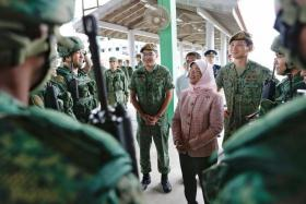 Madam Halimah Yacob interacted with some of the recruits who were doing SAR 21 weapon-handling drills.