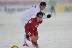 Uzbekistan's Otakhonov Abbosjon (in white) competes for the ball with Vietnam's Nguyen Cong Phuong.