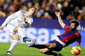 Real Madrid's Cristiano Ronaldo firing a shot as Levante's Ivi closes in.