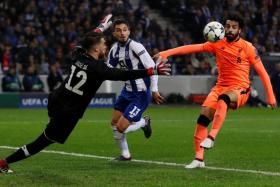 Liverpool's Mohamed Salah flicking the ball over Porto goalkeeper Jose Sa, before controlling it with his head and putting it across the line for their second goal.