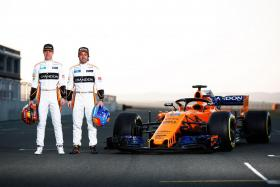 McLaren's Belgian driver Stoffel Vandoorne (left) and Spanish driver Fernando Alonso posing by their MCL33 car.