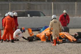 McLaren's Fernando Alonso (squatting) inspects his car after losing a rear tyre during testing.