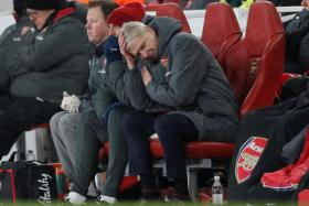 Arsenal manager Arsene Wenger cutting a frustrated figure on the bench.