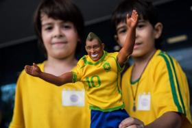 Two young Brazil fans with a figurine of Neymar outside the Mater Dei Hospital in Belo Horizonte, where the Brazilian superstar had a foot operation.