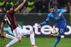 Arsenal's Henrikh Mkhitaryan shooting at goal as AC Milan's Lucas Biglia closes in.