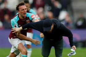 West Ham captain Mark Noble wresting a pitch invader to the ground.