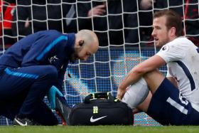 Harry Kane receiving treatment after suffering an ankle injury while playing against Bournemouth.